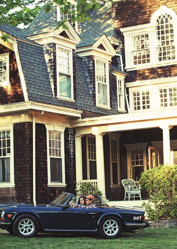 Gorgeous home with dark shingle siding and paneled white windows