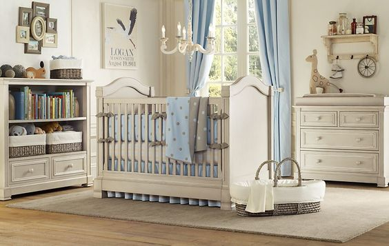Crib in the middle of the room under chandelier.
