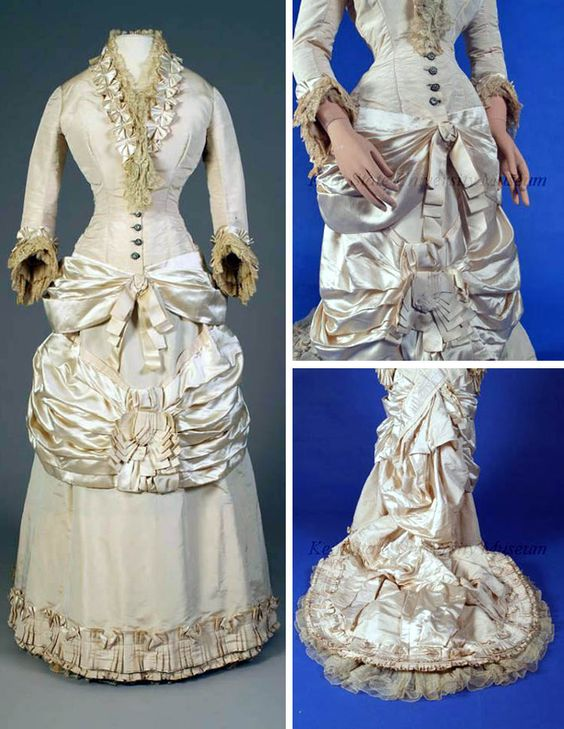 Wedding gown, American (attr.), ca. 1880s. White silk faille & satin. Fitted cuirass-style bodice, 3/4 sleeve, satin swag over hips. Semi-attached skirt with band of pleated and swagged satin across middle, hem with pleated faille trimmed with satin, long asymmetrical waterfall bustle and train. Kent State Univ. Museum website & Facebook