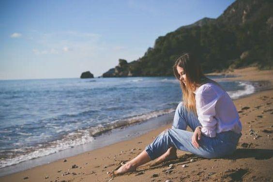 Mujer pensativa a la orilla del mar