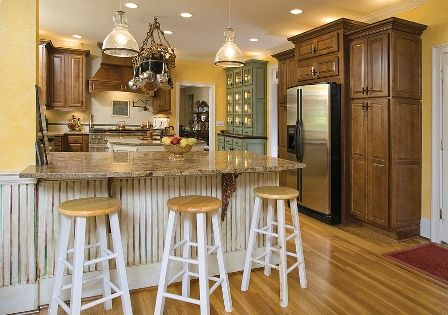 the idea of yellow walls... though not quite so bright!  the wood floor/wood cabinets/painted hutch/granite