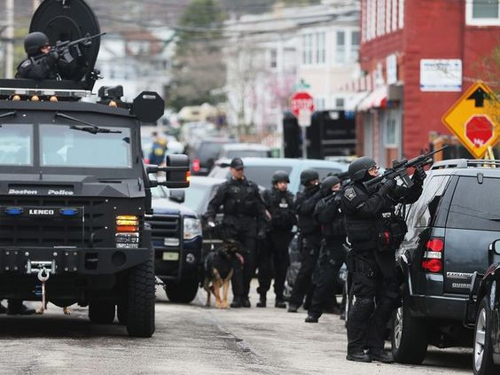 Boston police search for a suspect at a Watertown, Mass., apartment building.
