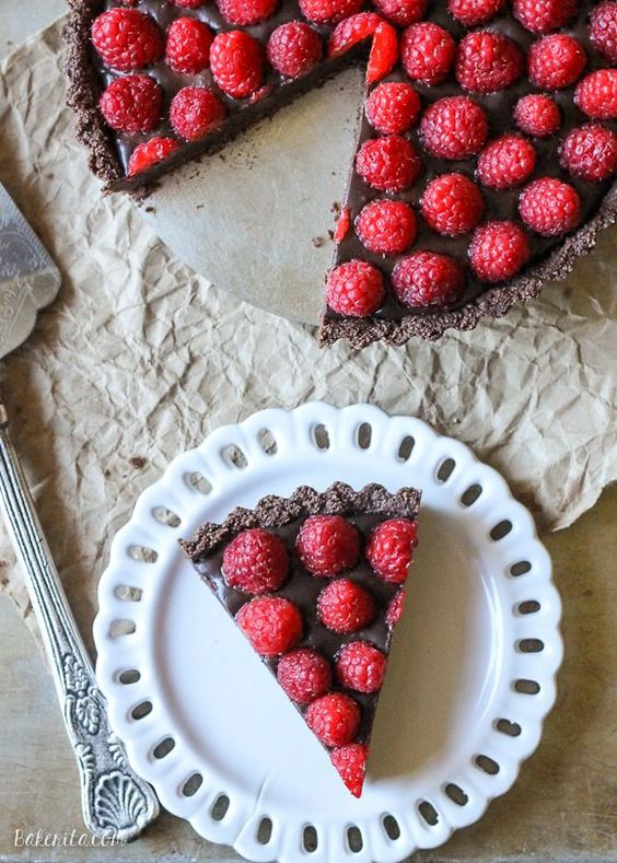 This No-Bake Raspberry Chocolate Tart comes together in just ten minutes! The no-bake chocolate crust is filled with vegan chocolate ganache and topped with fresh raspberries for a decadent, guilt-free treat. @bakerita