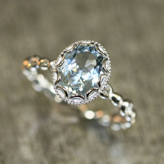 Stunning feminine and romantic! This aquamarine ring is crafted in solid 14k white gold with an 9x7mm oval shaped aquamarine set into a gorgeous