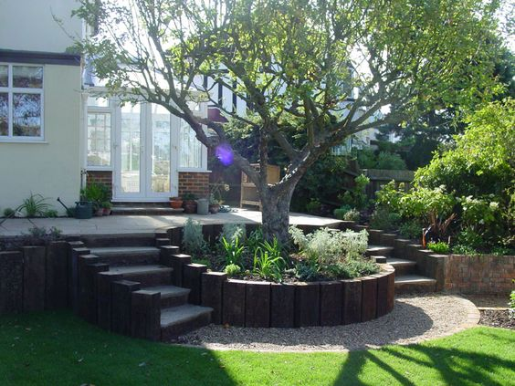 Circular wood planter boxes surrounding the trees for Curved garden wall ideas