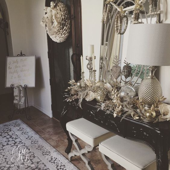 Silver and gold entry table with Wisteria stools and mercury glass candles sticks and ornaments