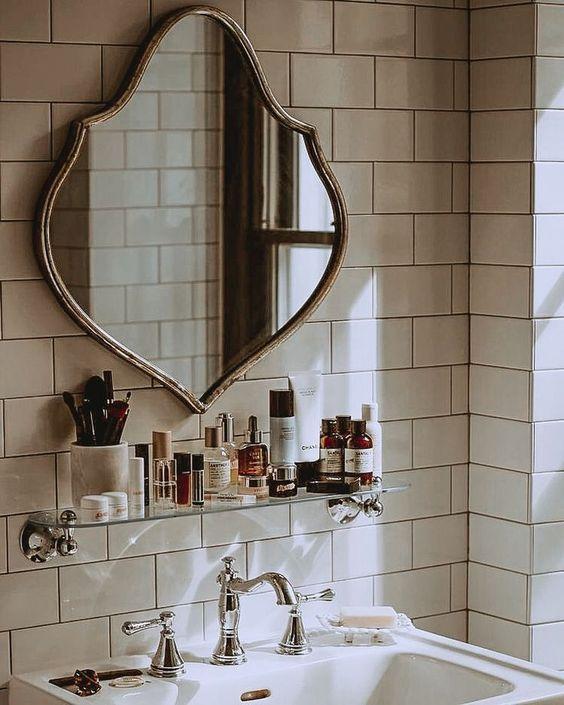 white subway tile backsplash in vintage bathroom design with pedestal sink and shelf over sink in neutral vintage bathroom, unique mirror in powder room decor
