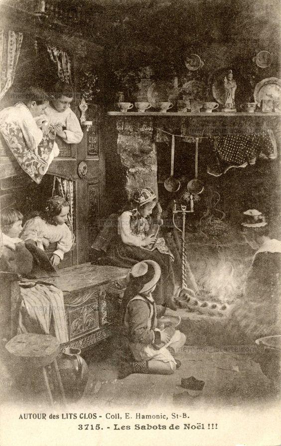 Les sabots de Noël !!! Dans une maison de Bretagne une mère entretient le feu dans la cheminée, les sabots des petits alignés sur l'âtre, les enfants dans le lit clos regardent (from https://mercipourlacarte.com/picture?/1454/)