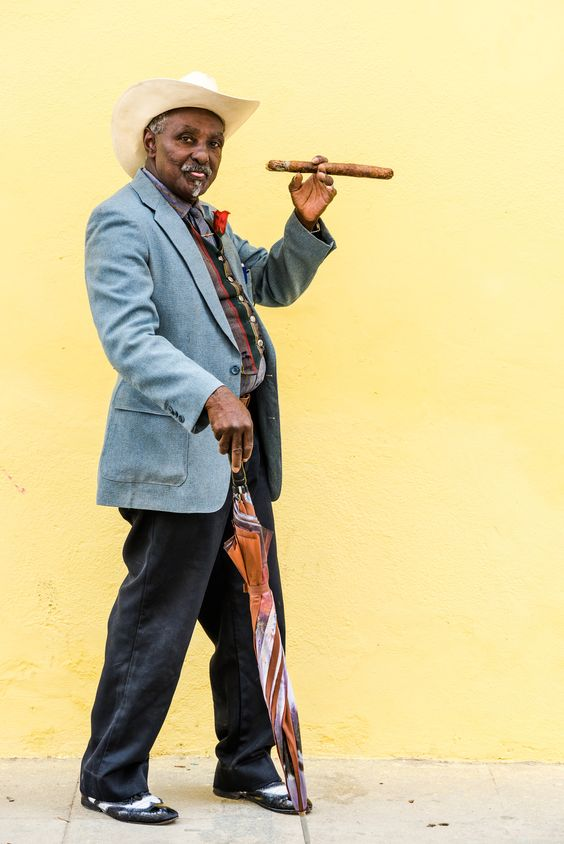 Cuban man smoking big cuban cigar in Havana, Cuba. - Havana, Cuba - September 27, 2015: Traditional Cuban man smoking big cuban cigar on yellow wall background in Havana, Cuba - All About Cuba http://www.Cuba-Junky.com