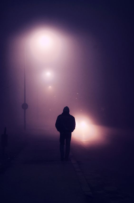 Fog - Silhouette of a young man walking down the street on a foggy evening