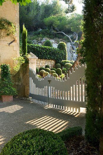 Garden gate ideas and French Country garden inspiration: Picket fence style garden gates lead to magnificent lush French garden with boxwoods. #gardengate #frenchcountry #frenchfarmhouse #gardeninspiration #boxwoods