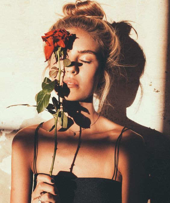 This is an image of a youthful girl showing a rose as a symbol of age.: