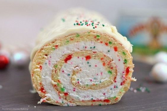 A simple vanilla roll cake with red and green dots and spirals of creamy buttercream is the perfect dessert for Christmas parties.