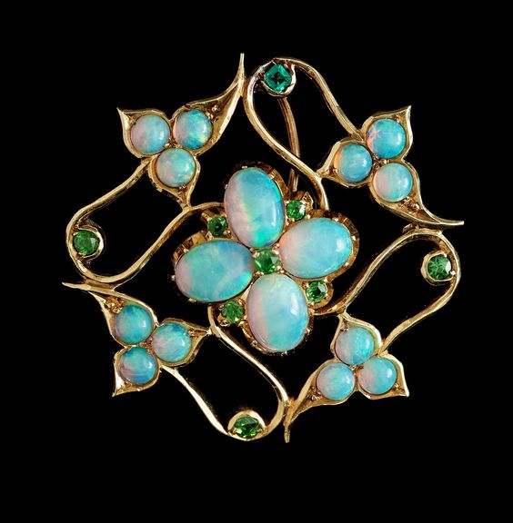 AN ARTS AND CRAFTS OPAL AND DEMANTOID GARNET BROOCH. Probably England ca 1910. 15K gold. Length 38 mm.