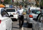 23.set.2015 - O ambulante Jairo Rosendo de Freitas vende água, usando trajes de garçom, no farol da Avenida Interlagos esquina com a Rua José Neves, na zona sul de São Paulo. Jairo trabalha todos os dias das 8h às 18h, com seu jeito diferenciado para chamar a atenção dos motoristas que passam pela avenida
