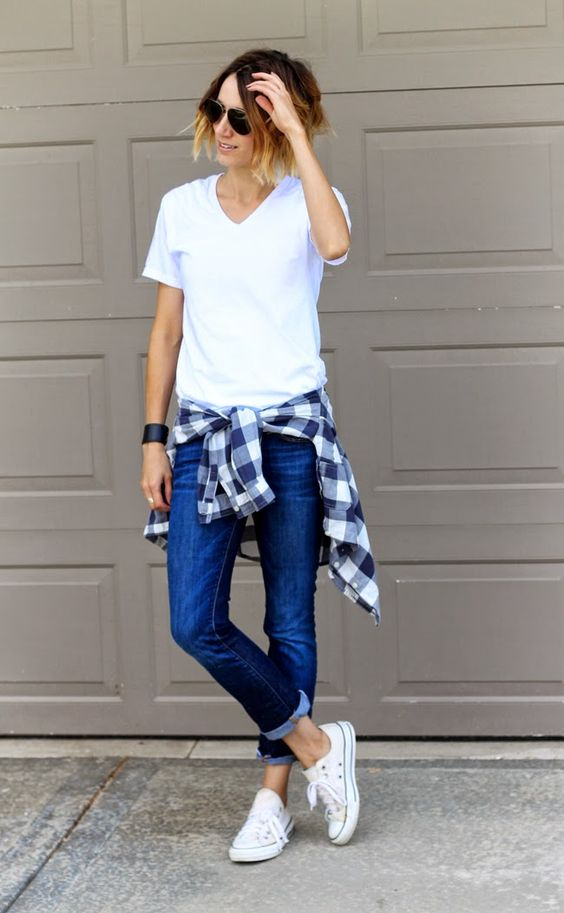 White v-neck, dark denim and a plaid shirt tied around the waist: