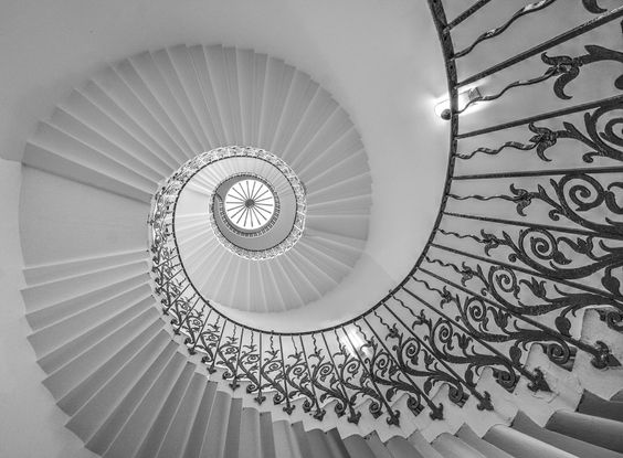 https://flic.kr/p/qP9X61 | 9558 | The Tulip Stairs   Looking up the Tulip staircase.   The elegant Tulip Stairs in the Queen's House are the first geometric self-supporting spiral stair in Britain. Although called the 'tulip' stairs, it is thought that the stylized flowers in the wrought-iron balustrade are actually fleurs-de-lis, as this was the emblem of the Bourbon family of which Queen Henrietta Maria (wife of Charles I) was a member.