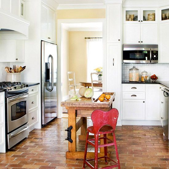 A worn wooden chemistry-lab table acts as a kitchen island in this space. More inspiration: http://www.bhg.com/kitchen/island/island-design-ideas/?socsrc=bhgpin062312#page=1