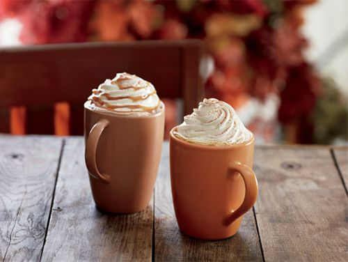 two orange mugs with whipped cream on a wooden table with autumn leaves