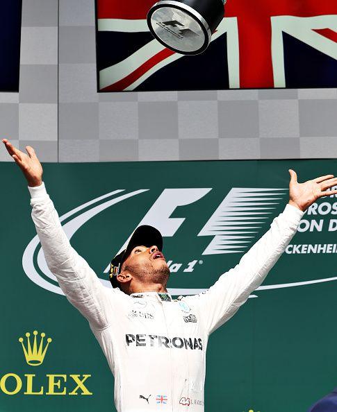 Lewis Hamilton of Great Britain and Mercedes GP celebrates his win on the podium…