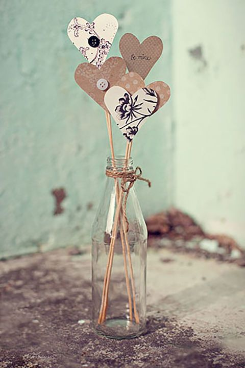 Hearts on a Stick:  Simply cut out some scrapbook paper hearts, attach them to a wooden skewer, and display 'em all in an old bottle to add a bit of charm to your dresser.