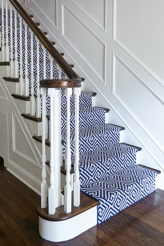Navy and White geometric runner by Stark Carpet for this classic 1920's home. Custom White wall paneling and painted white risers. Designed by SHOPHOUSE Interiors. www.shophousedesign.com