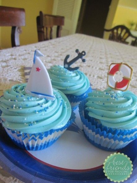 Beach Sail Boat Birthday Cupcakes.  Blue and White Cupcake wrappers with light blue swirls of frosting.  There are fun blue and white sprinkles on top.  I included an assortment of beach themed cupcake pics including sail boats, anchors and life savers.