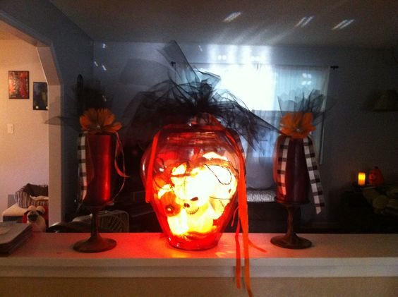 Pumpkin and skull lights in a vase wrapped in black tule and tied with ribbon. So easy and so festive.