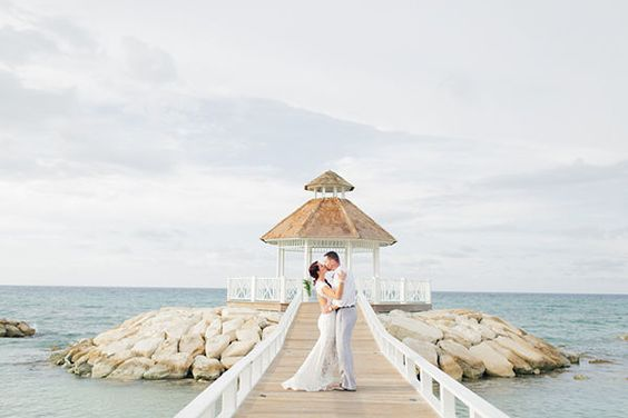 The bride and groom kiss on the dock leading towards gazebo by the ocean at this Jamaica destination wedding.