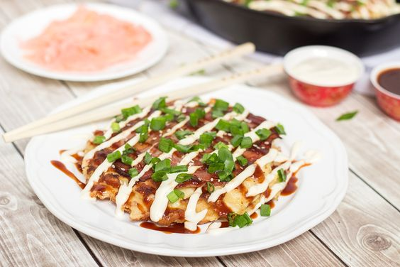 This traditional Japanese pancake (Okonomiyaki) is filled with cabbage and topped with sliced pork and amazing sauce!   cookingtheglobe.com