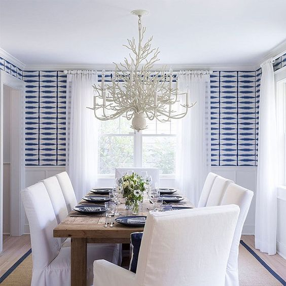 coastal beach style dining room with blue and white geometric wallpaper above white wainscoting, white dining chair covers, white pendant light: