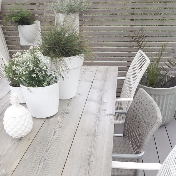 ♡ Outdoor eating area with washed wood furniture, fence and deck mixed with white planters
