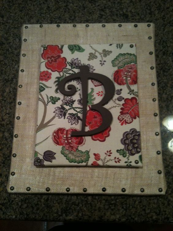 Wall hanging. Covered large canvas in burlap and added nail tacks.  Covered smaller canvas with cloth napkin.  Then added painted letter.  Hot glued it together.