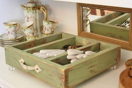 An old drawer re-purposed into a tray for silverware or serving pieces. Note the antique knobs on the bottom of the drawer, which gives it character and height.: