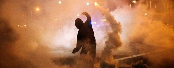 A protester throws a tear-gas canister back toward riot police after a 10 p.m. curfew went into effect in Baltimore. (David Goldman/AP)