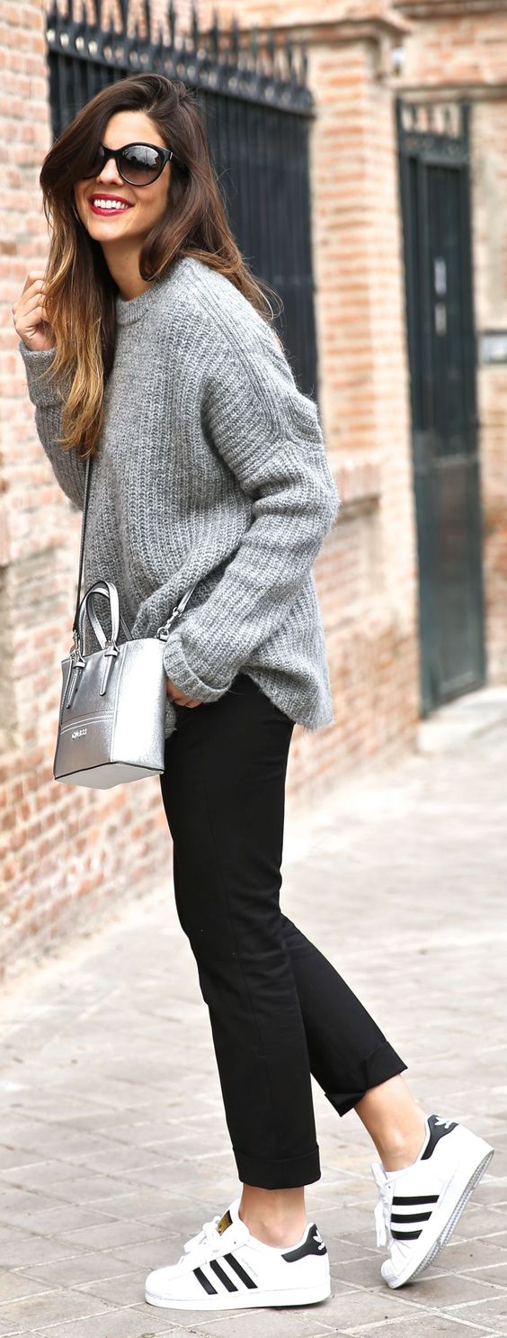 Natalia Cabezas is wearing a grey knit sweater and black trousers from Zara, sneakers from Adidas, sunglasses from Prada and the bag is from Guess: