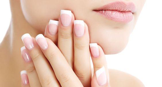 unas manos con uñas perfectamente cuidadas, con manicura francesa y limadas en cuadrado posadas sobre la mandíbula