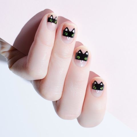 For this black cat look, start with a stripe of black polish to the middle of your nail. At the top of each strip, add two triangles and let dry. Add white dots to the ears and below for the cat's tongue. Place two green dots to the middle for the cat's eyes, then paint thin black lines at an angle to give each nail signature cateyes. Finish with a topcoat.  Design by @formulaxnail