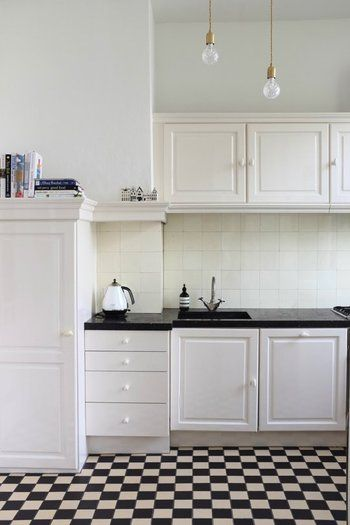 床にブロックチェックのタイルを貼って、全体をブラック&ホワイトでまとめたモダンなキッチン。