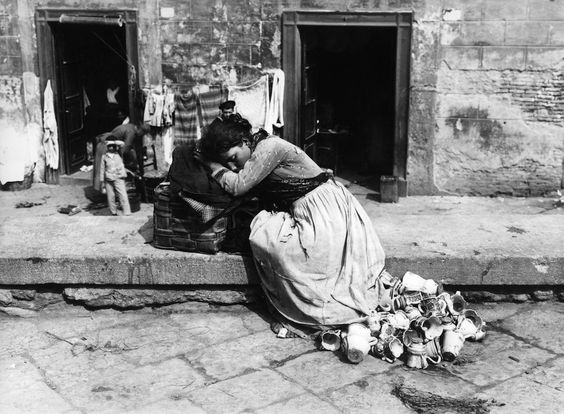Una ragazza che vende tazzine e altri oggetti di ceramica si riposa in una strada di Napoli, verso il 1885.