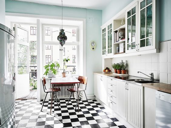 Kitchen with black and white floor and light blue walls