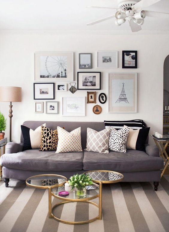 Gallery wall over the sofa with black and white prints, a striped neutral rug, and mixed print throw pillows -- a stylish way to prove that neutrals never have to be boring!: