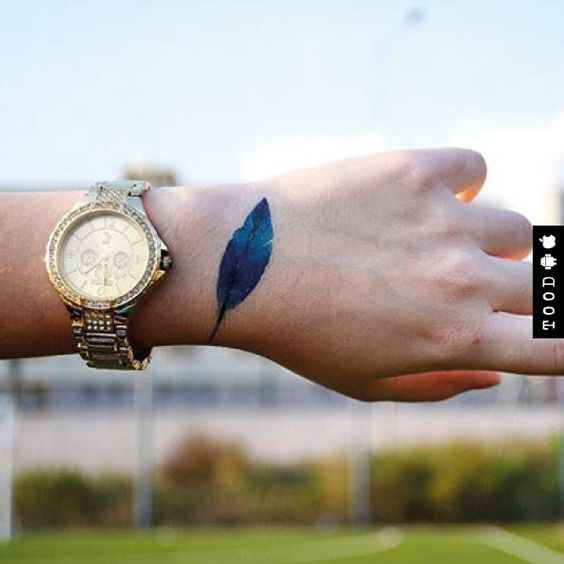 Blue feather temporary tattoo sticker on wrist