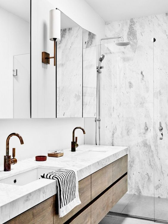 Minimalist bathroom with marble walls and a floating credenza:
