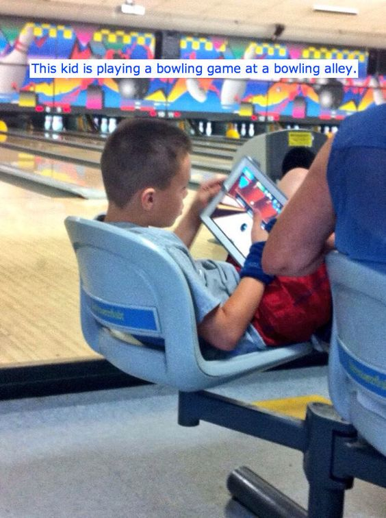 Some children. Playing a bowling game on his ipad while at a bowling alley | 45 Photos That Will Annoy You More Than They Should: