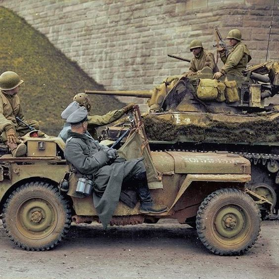 Two                                                          high-ranking                                                          German                                                          Wehrmacht                                                          officers being                                                          transported                                                          under the                                                          watchful eye                                                          of soldiers                                                          from the 4th                                                          Armored                                                          Division in a                                                          Ford GPW jeep,                                                          pass by a                                                          camouflaged M5                                                          Stuart                                                          light-tank                                                          belonging to                                                          the 37th                                                          Armored                                                          Regiment                                                          during the                                                          surrender in                                                          Hersfeld,                                                          Germany, 31st                                                          of March,                                                          1945.