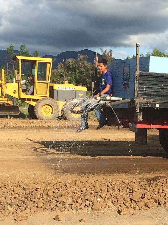Camión cisterna mojando el Material colocado para compactar