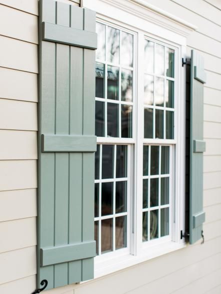 Handmade custom shutters give the front of this welcoming and well-detailed home a cottage feel.