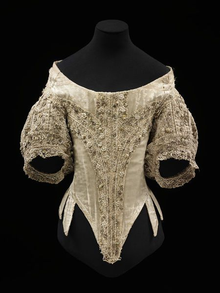 Pale-coloured silk satin bodice, 1660-1669, V&A. Decorated with parchment lace. The boned foundations is made from twelve pattern pieces, reinforced at places with up to three extra layers of linen. The middle side panel is unboned but stiffened with buckram and wool and may be a later addition to increase the size...