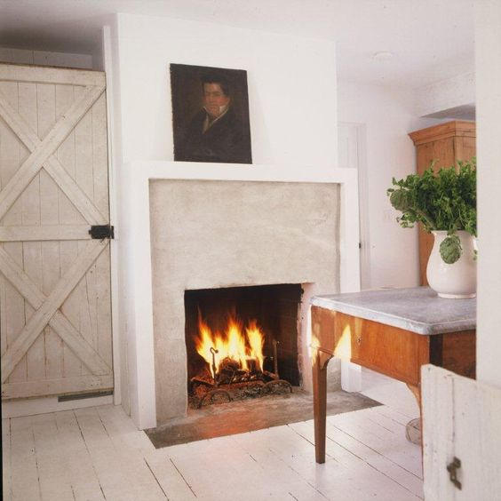 A gorgeous white kitchen by Darryl Carter with primitive fireplace, rustic door, and timeless design. #whitekitchen #primitive #darrylcarter #countrykitchen #timeless